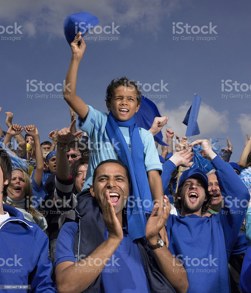 Stadium crowd cheering, boy (5-7) on father's shoulders, waving cap stock photo