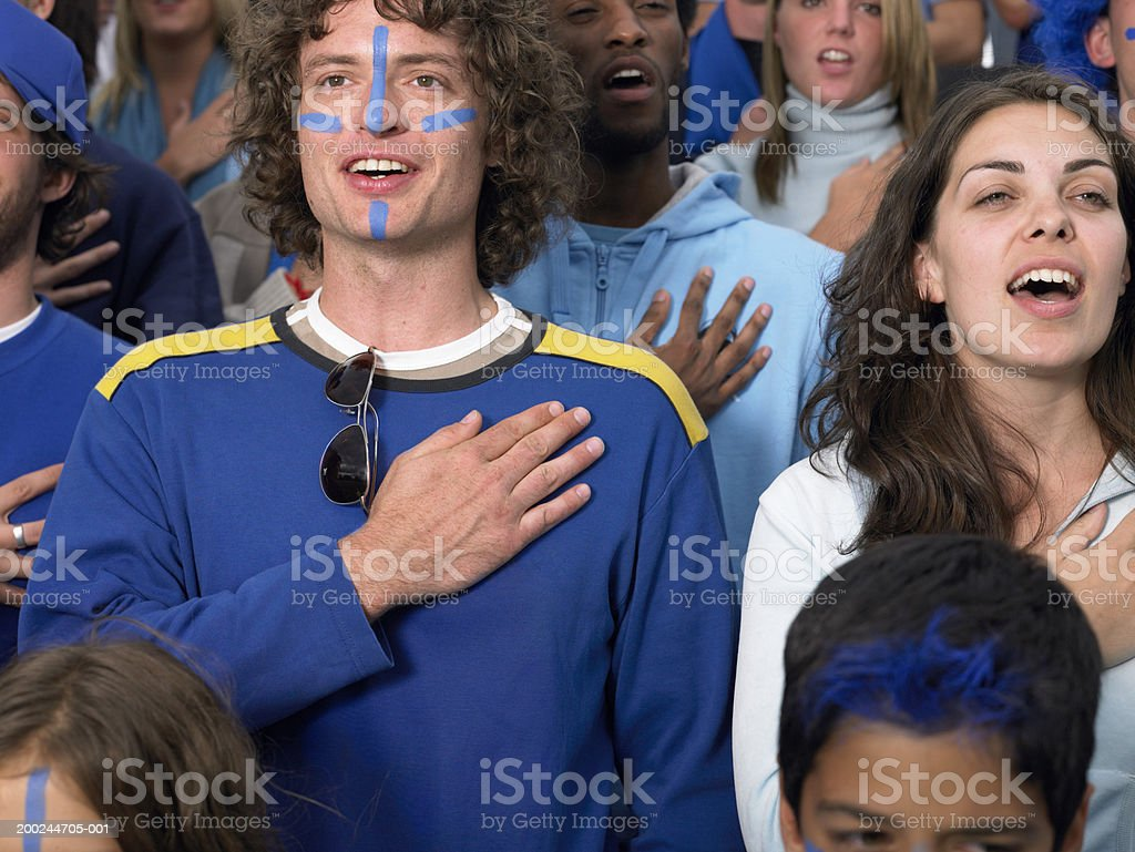 Stadium crowd, fans singing with hands held over heart, close-up stock photo