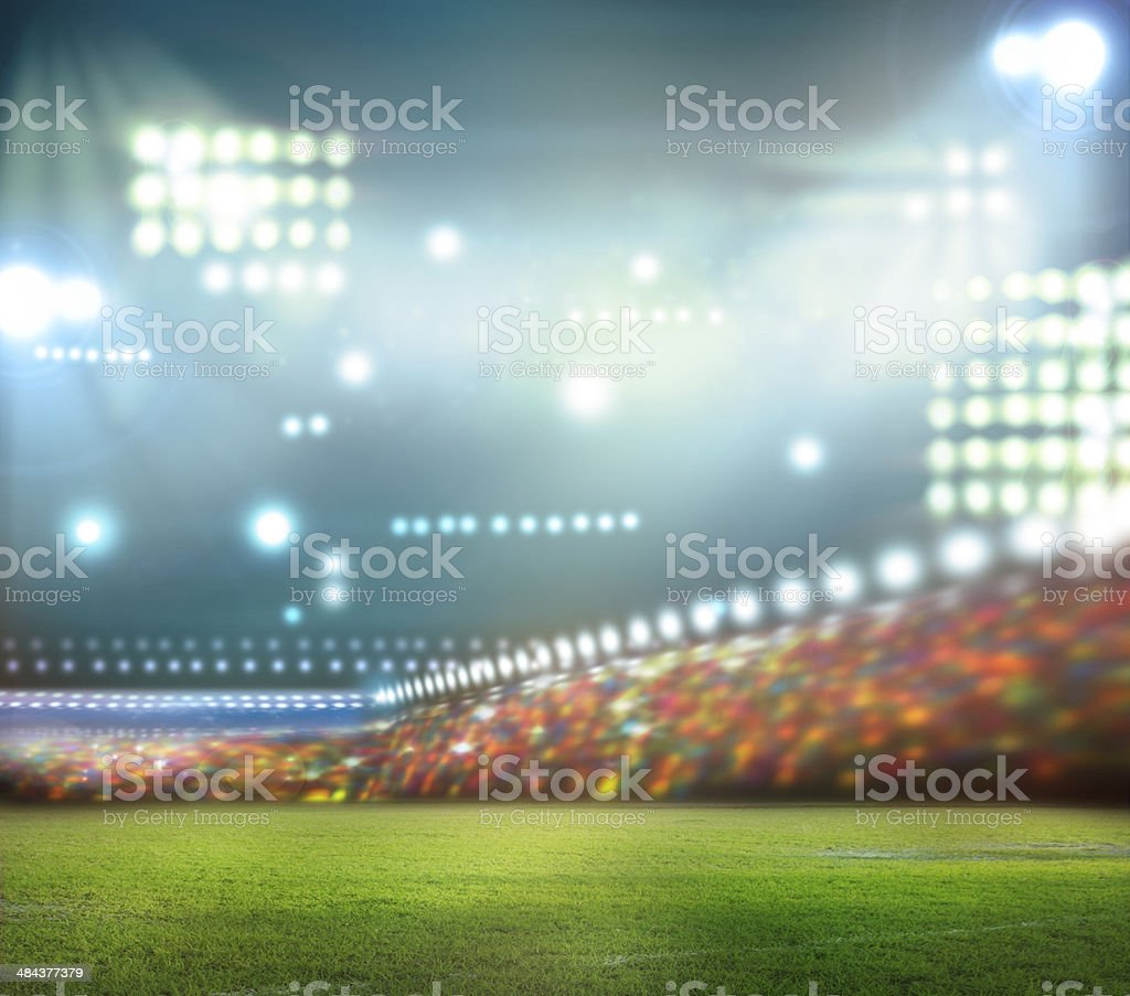 Stadium lights shining down on field at night stock photo