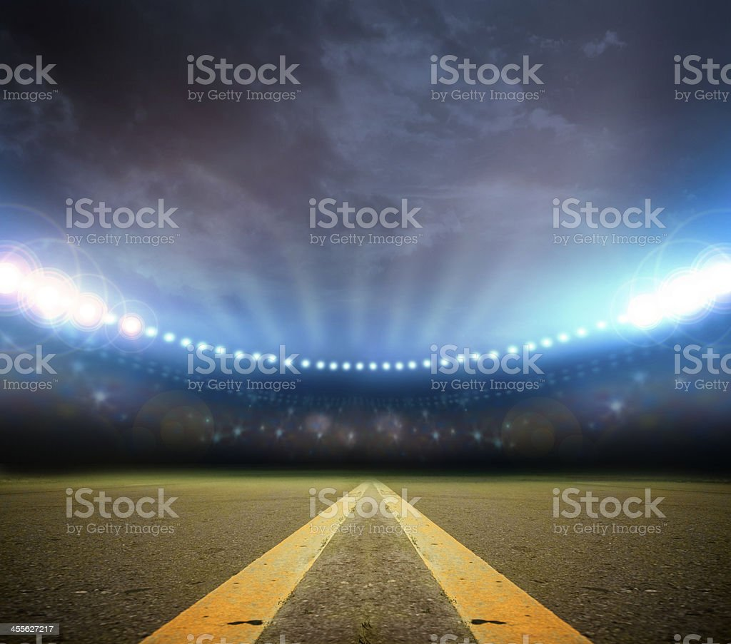 A stadium lit up with a road coming down the middle stock photo