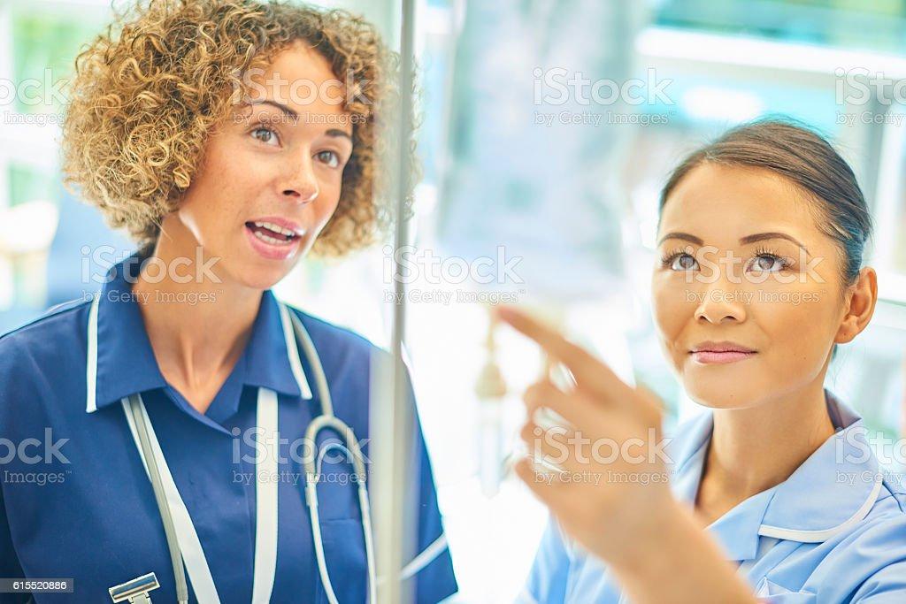 staff nurse advising young nurse stock photo