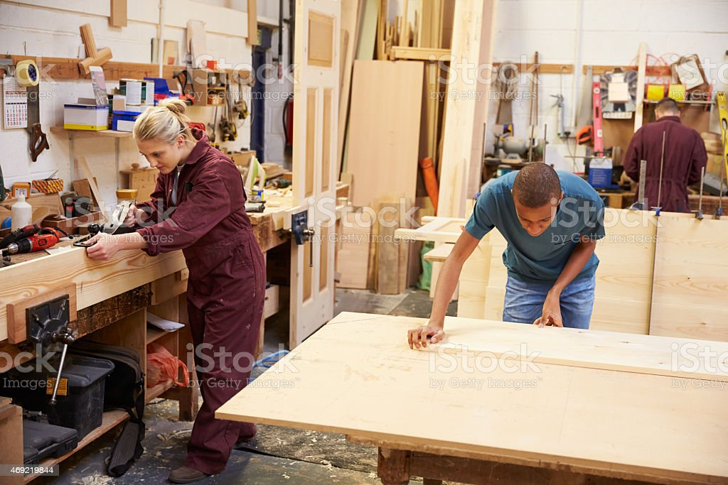Staff Working In Busy Carpentry Workshop stock photo
