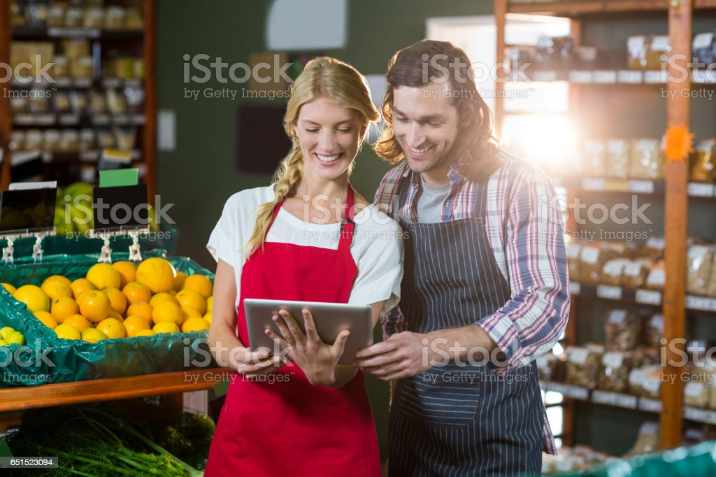 Staffs using digital tablet in organic section stock photo