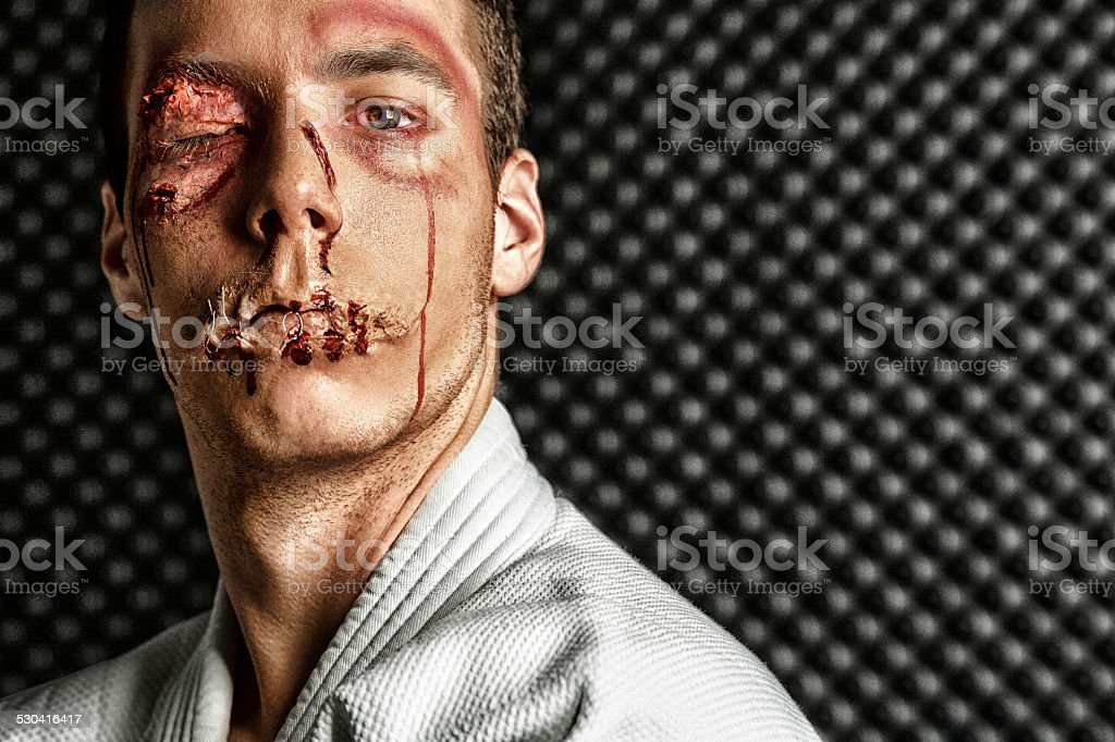 Stage makeup beaten face   Young man   Wearing martial arts outfit stock photo