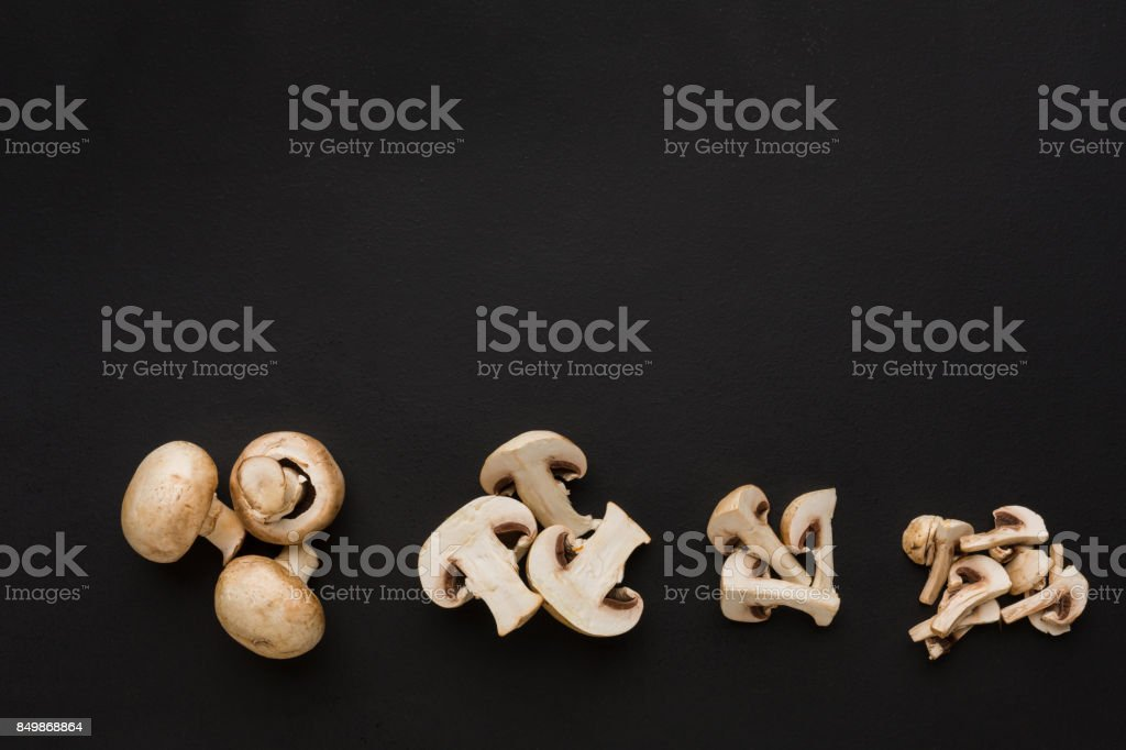 Stages of cutting mushrooms on black background stock photo