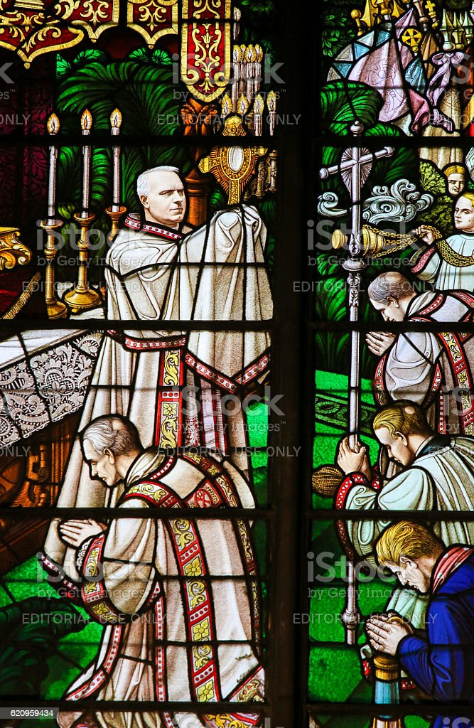 Stained Glass - a bishop holding a Monstrance stock photo