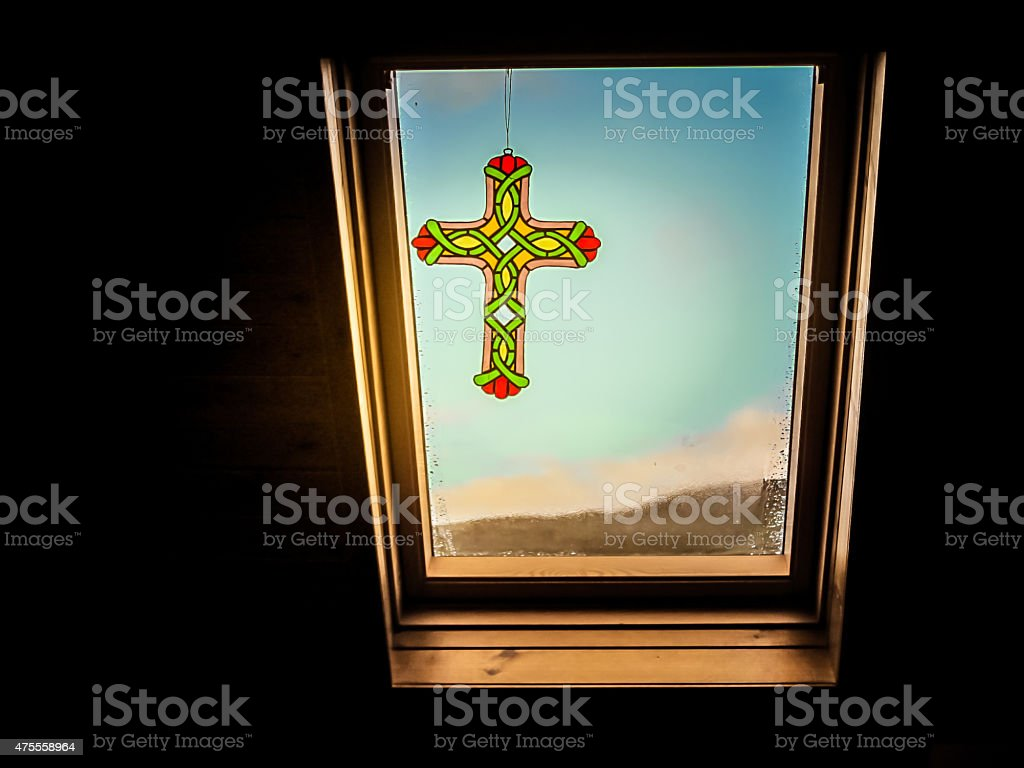 Stained Glass Christian Cross over Glass Window with Bright Sunlight stock photo