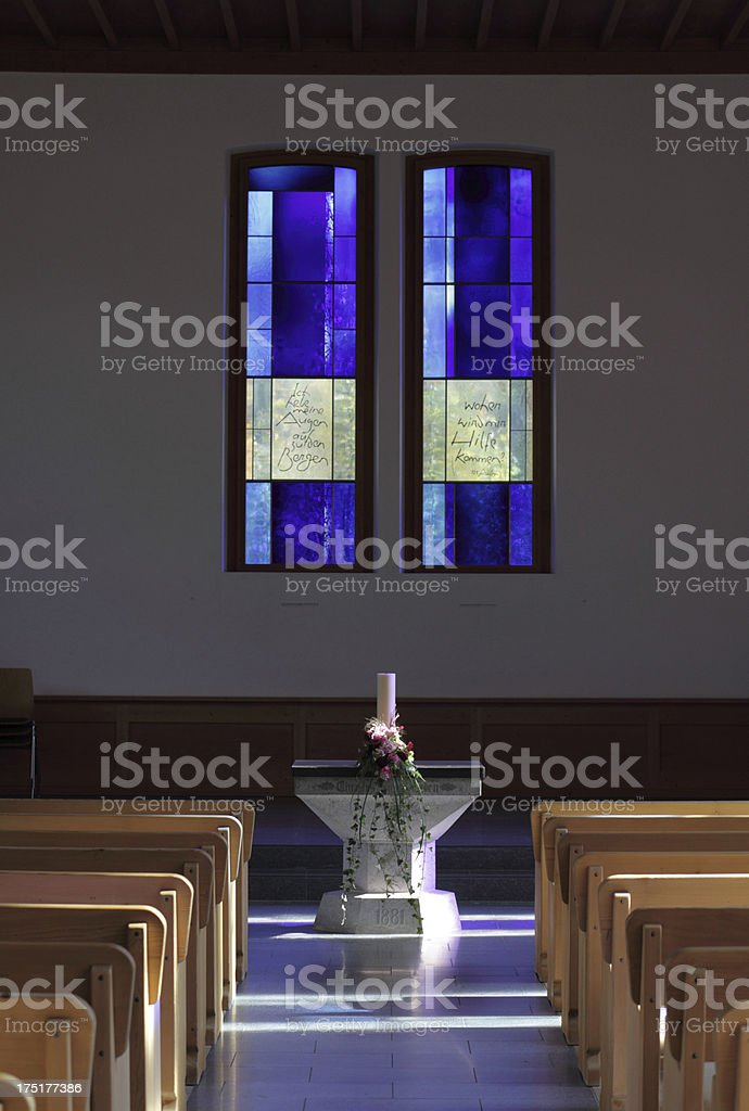 stained glass church window with font and pews royalty-free stock photo