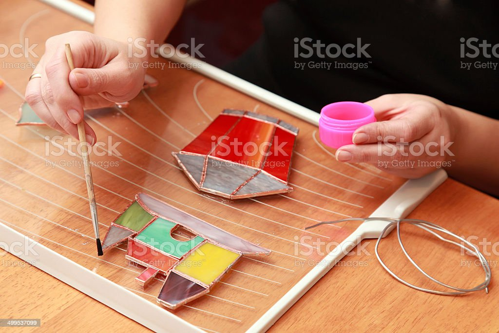 Stained glass maker works with colorful souvenirs stock photo