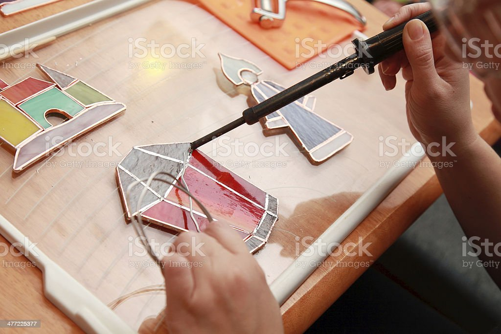 Stained glass maker works with red lamp souvenir stock photo