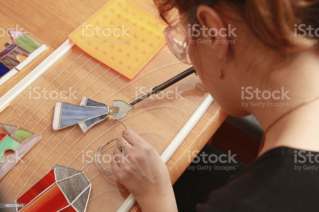 Stained glass maker works with small colorful souvenirs stock photo