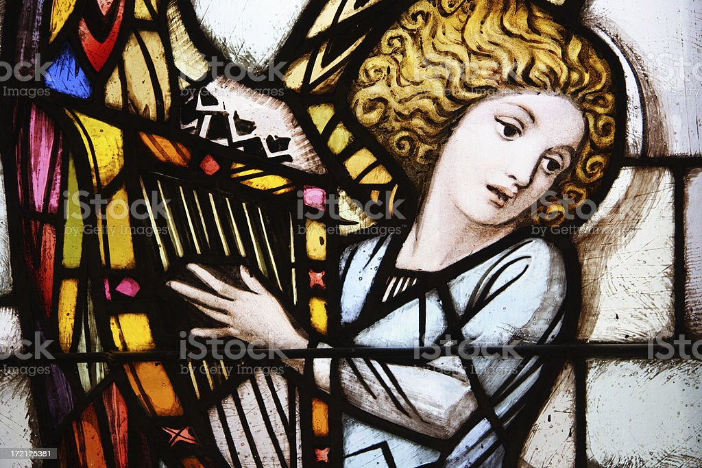 Stained glass window of angel playing the harp stock photo