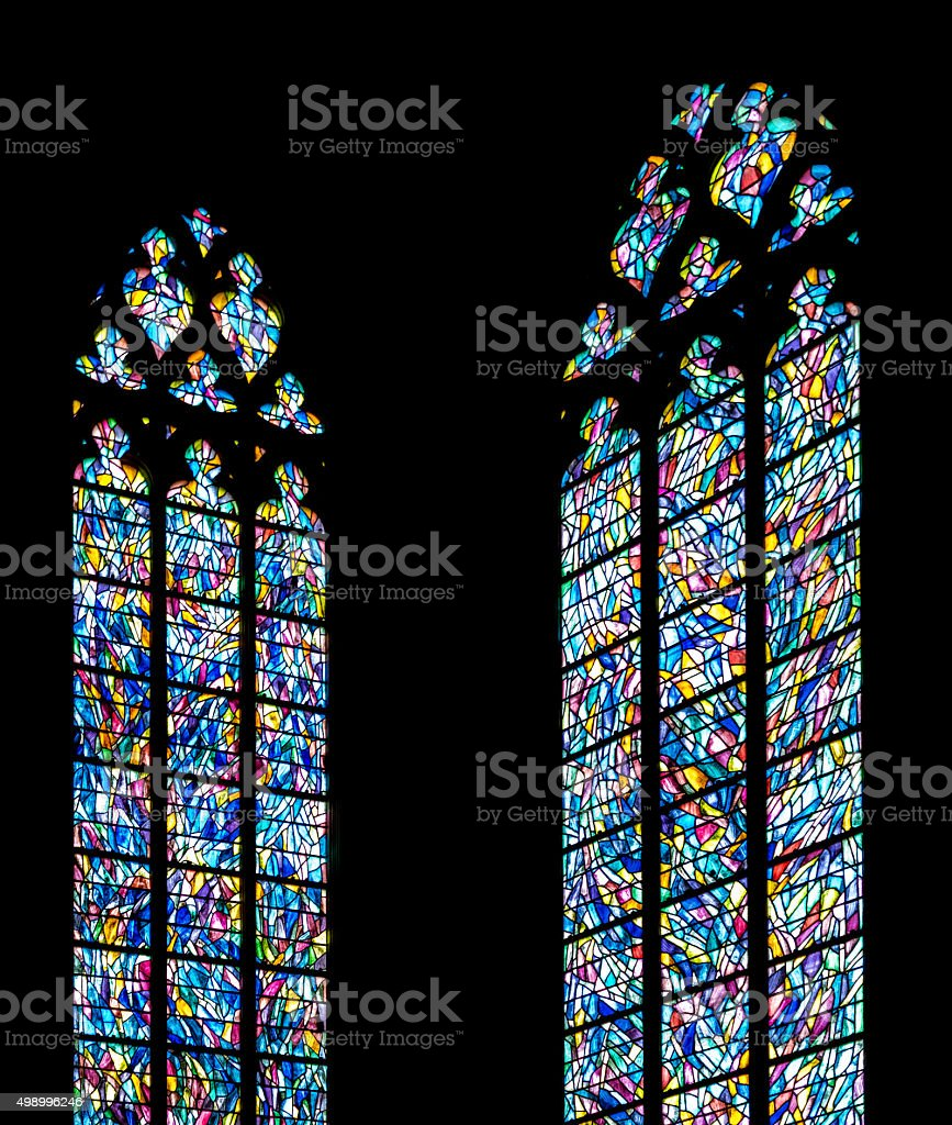 Stained glass windows against a silhouette church wall stock photo