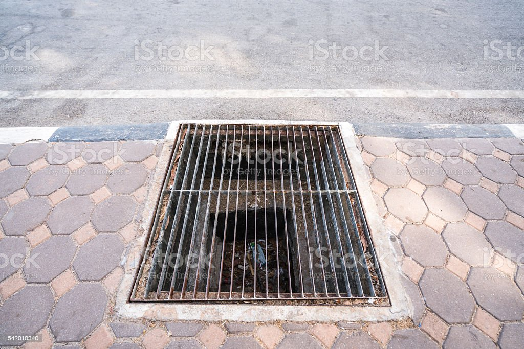 Stained steel grill sewer cover on public footpath stock photo