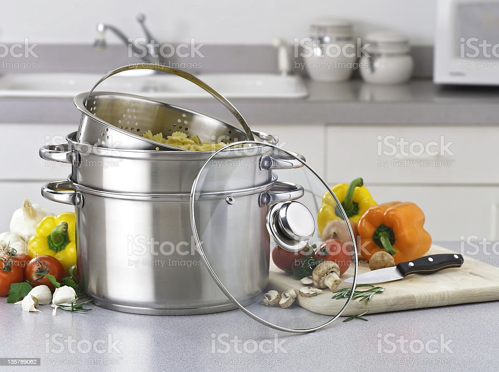 Stainless pasta pot on kitchen counter with fresh vegetables stock photo