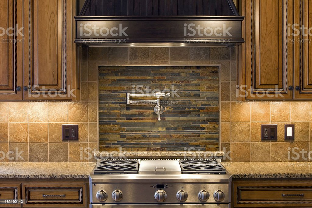 Stainless Residential Kitchen Range with Pot Faucet, Tile & Cabinets stock photo