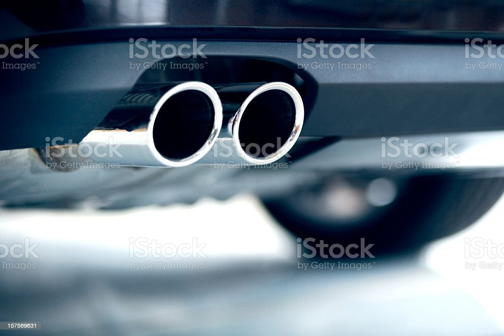 Stainless steel exhaust pipes on a blue car stock photo