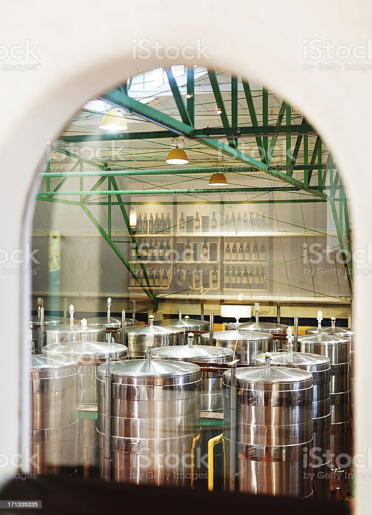 Stainless steel fermentation vats and reflected wine bottles at winery royalty-free stock photo