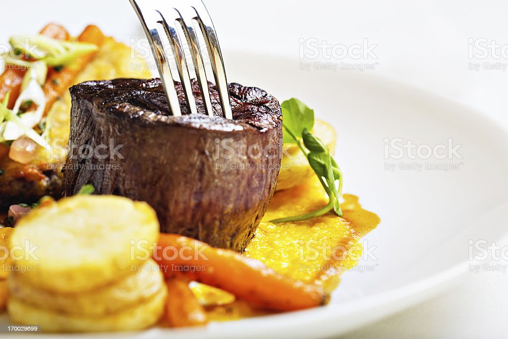 Stainless steel fork tests tenderness of grilled filet mignon stock photo