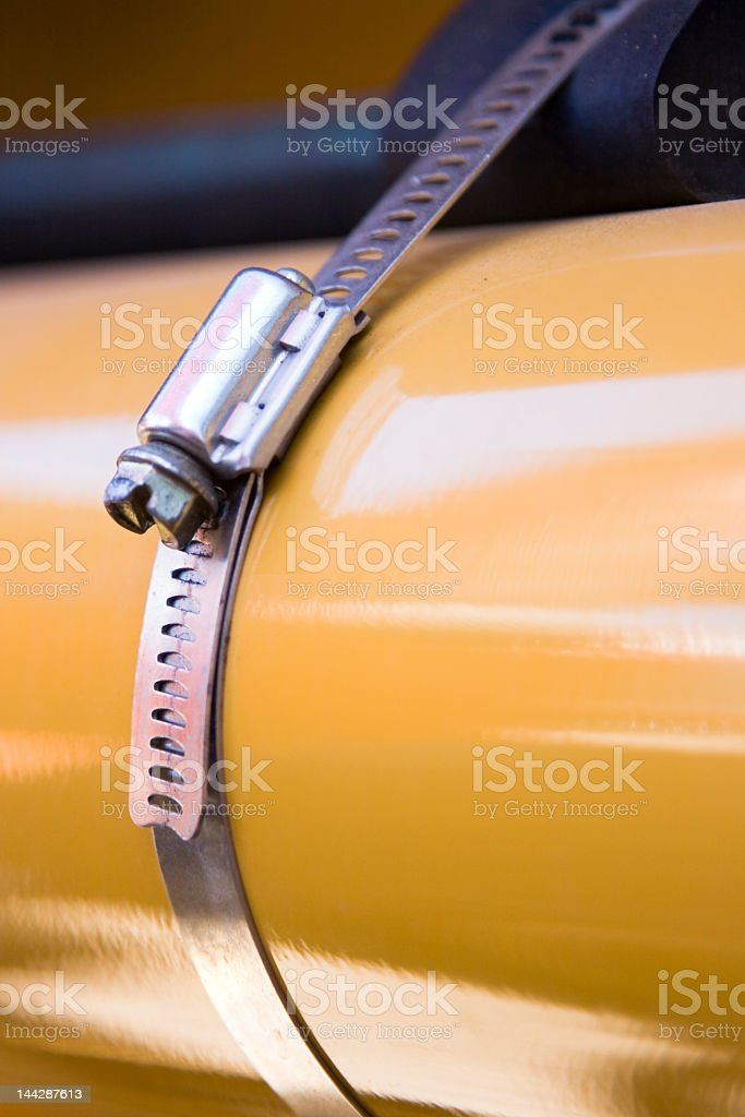 Stainless steel hose clamp and yellow metal pipe royalty-free stock photo