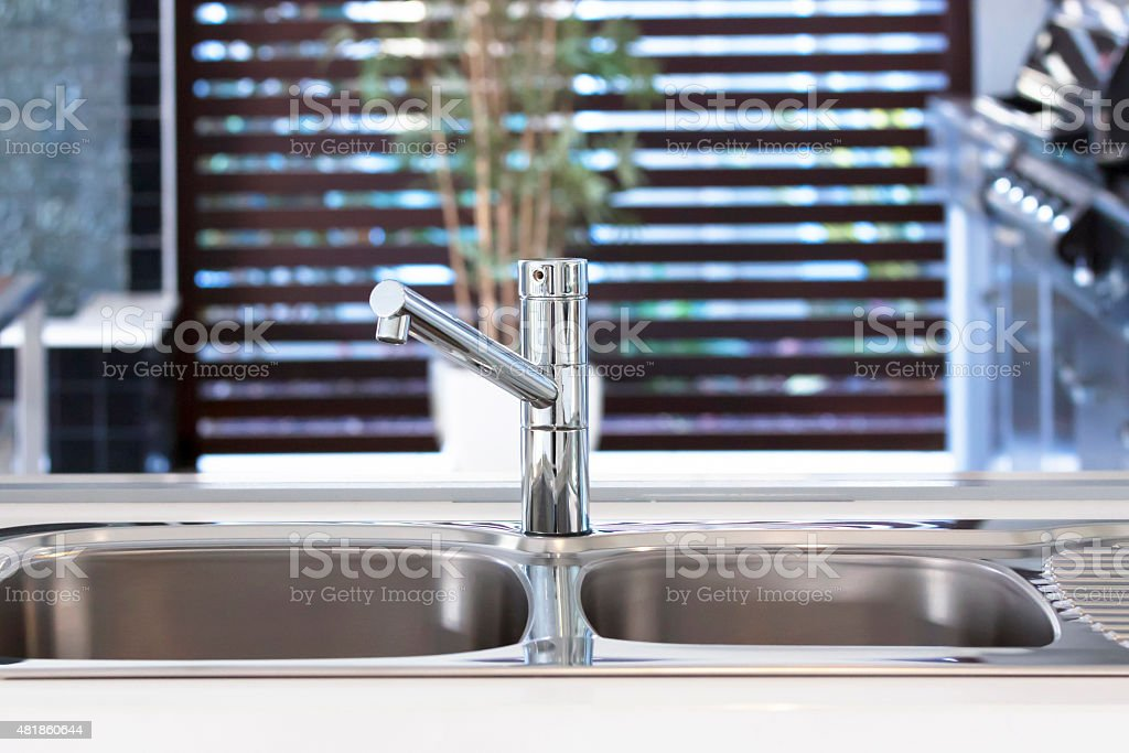 Stainless steel kitchen mixer tap and kitchen sink stock photo
