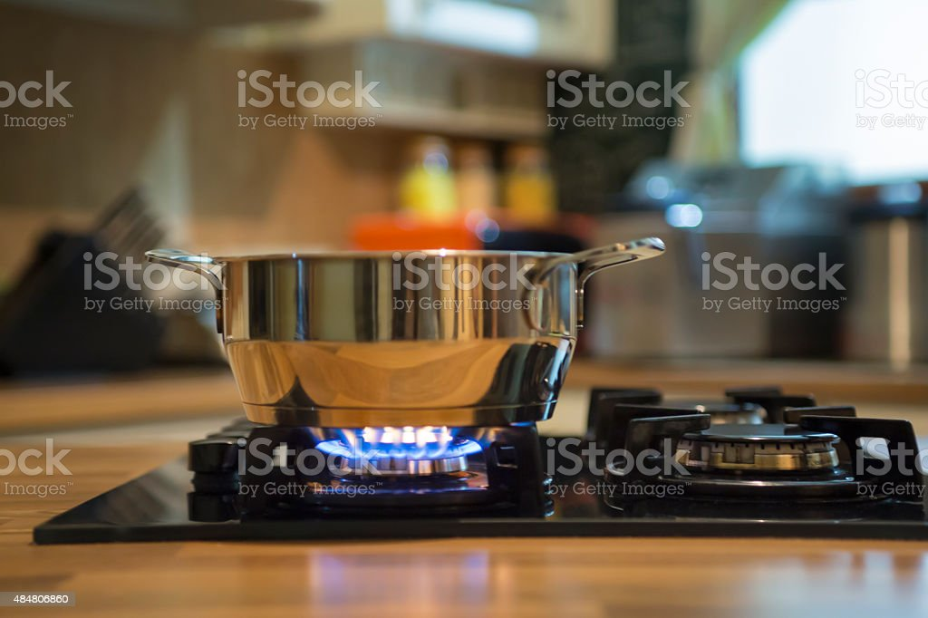 Stainless steel saucepan on gas stove burner. stock photo