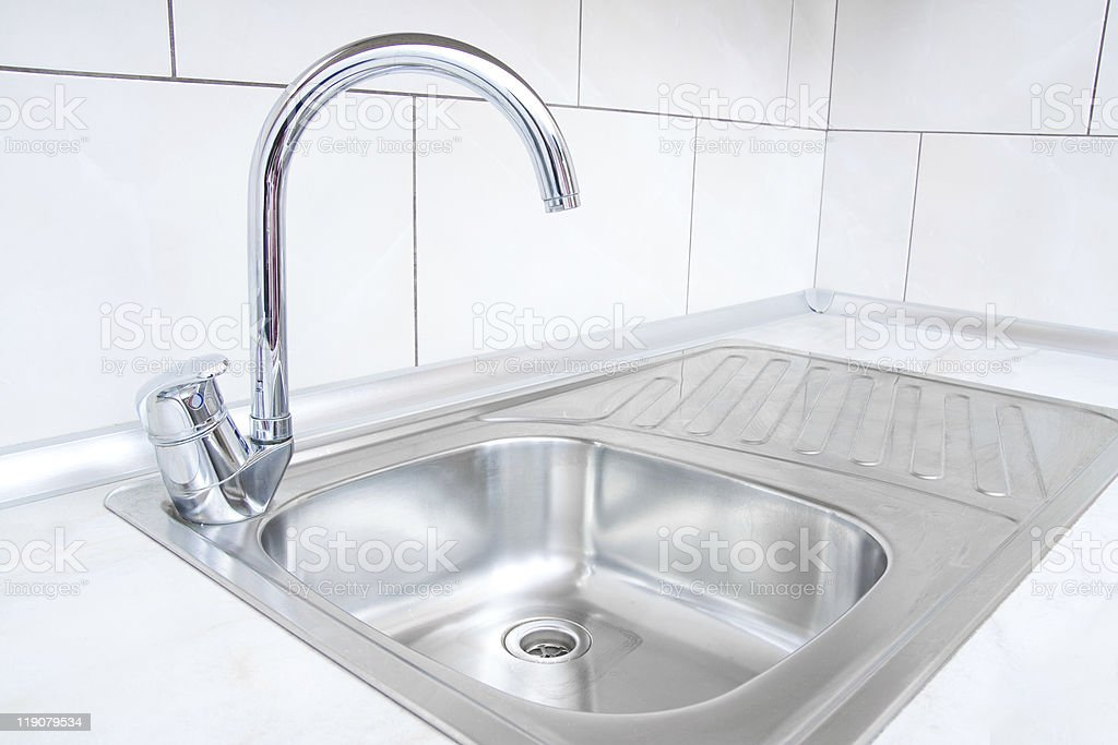 Stainless steel water basin with arched silver faucet stock photo