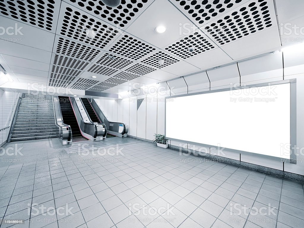 A staircase and an escalator with a white billboard stock photo