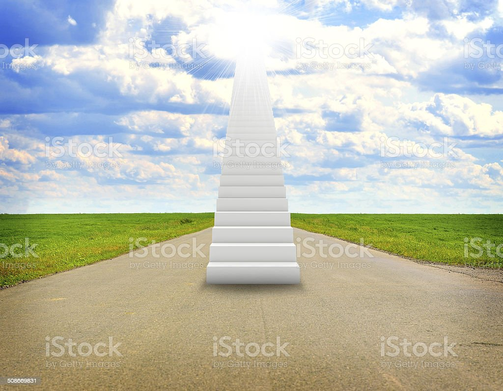 Stairs in sky with green grass, road and clouds stock photo