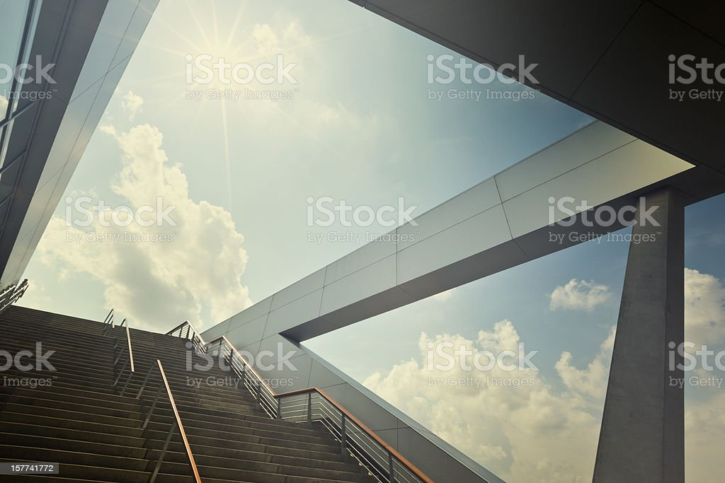 A stairway leading up to blue sky with sun over light cloud royalty-free stock photo