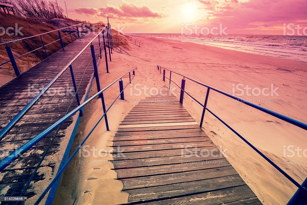 Stairway to the sandy beach at sunset stock photo