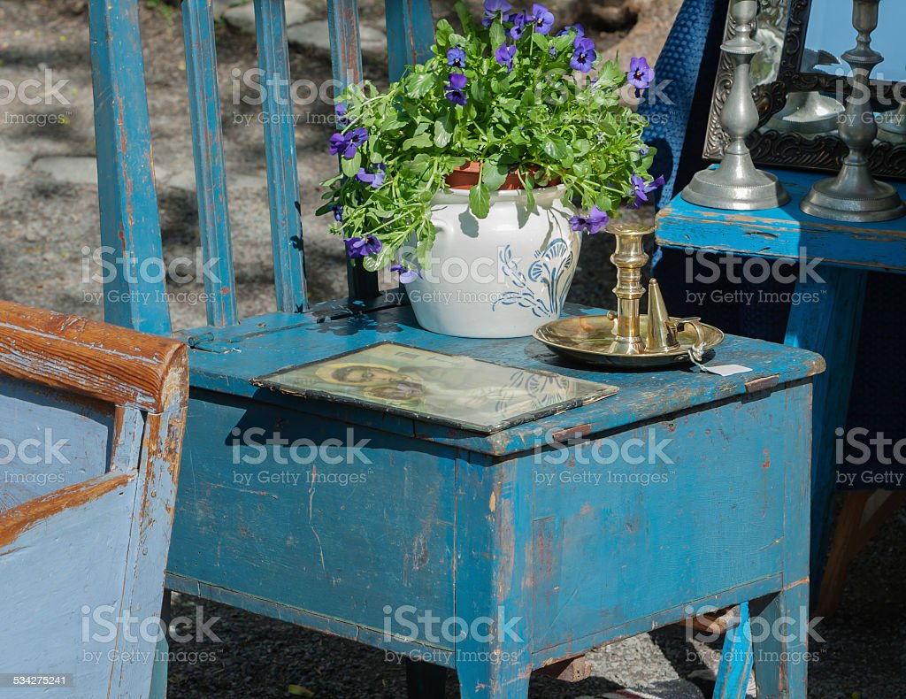 Stand at an outdoor market with antique wooden furniture. stock photo