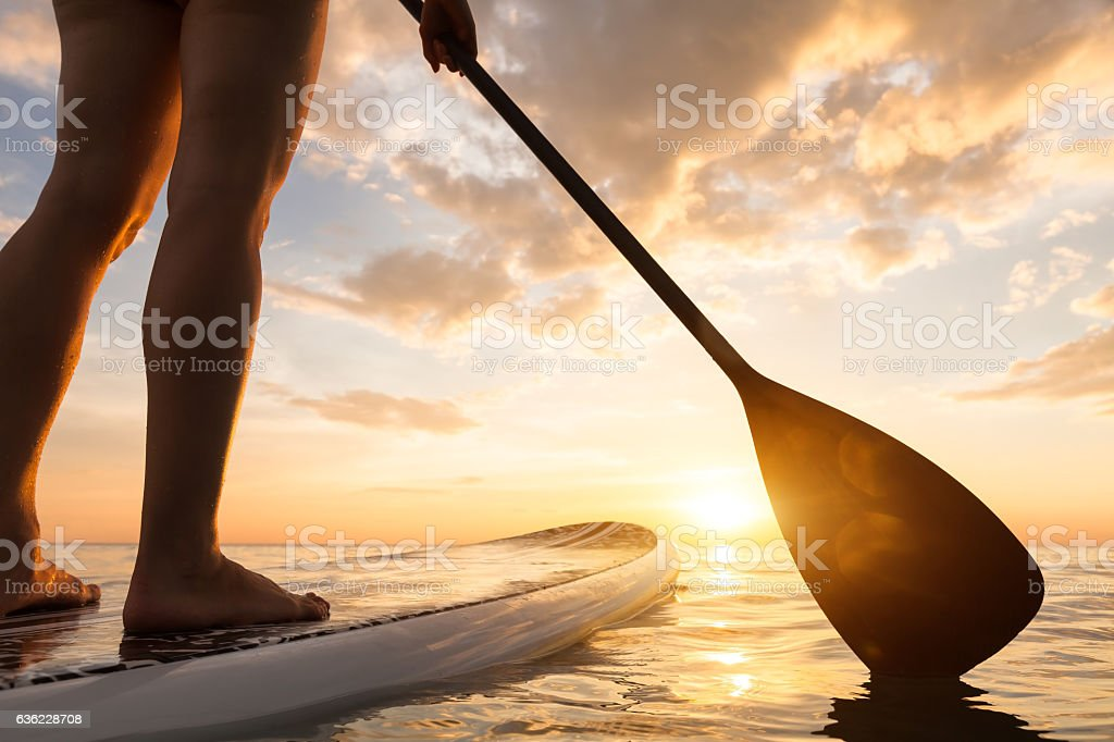 Stand up paddle boarding on quiet sea, legs close-up, sunset stock photo