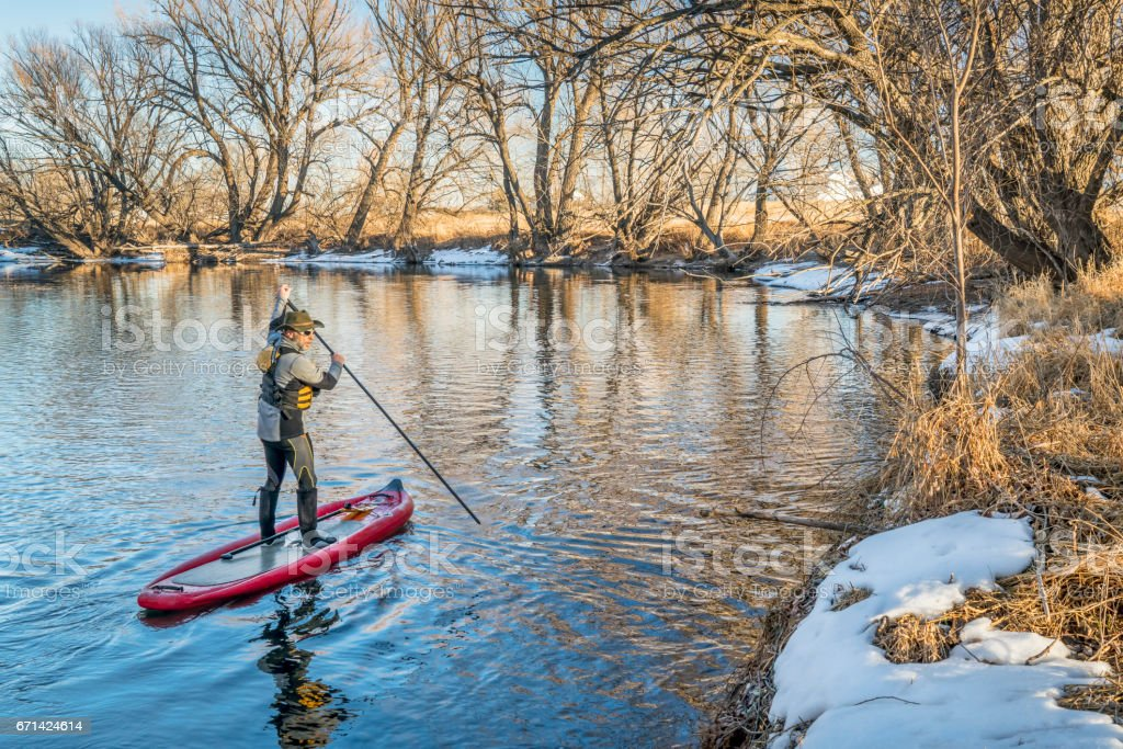 Stand up paddler poling on shallow river stock photo