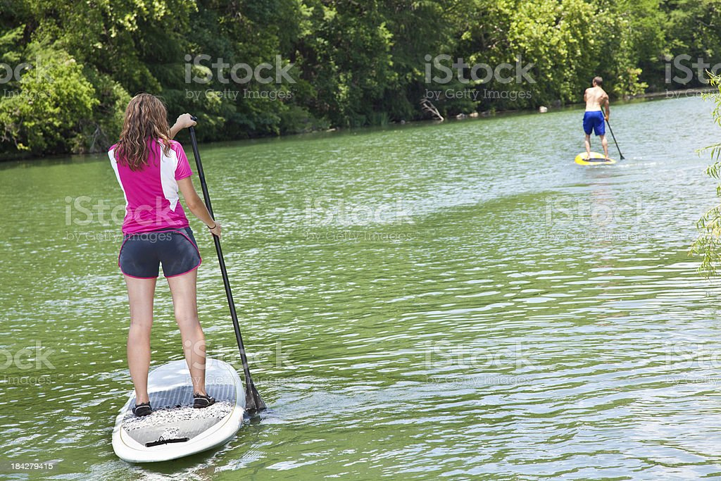 Stand Up Paddlers Paddling Down a River royalty-free stock photo