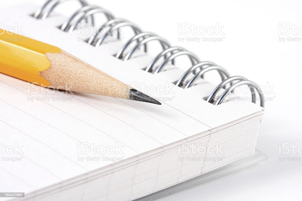 Standard sharpened pencil placed on spiral bound notebook stock photo