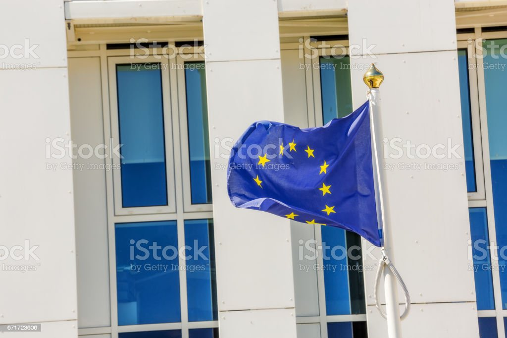 Standard waving flag of the European Union with building business on background stock photo