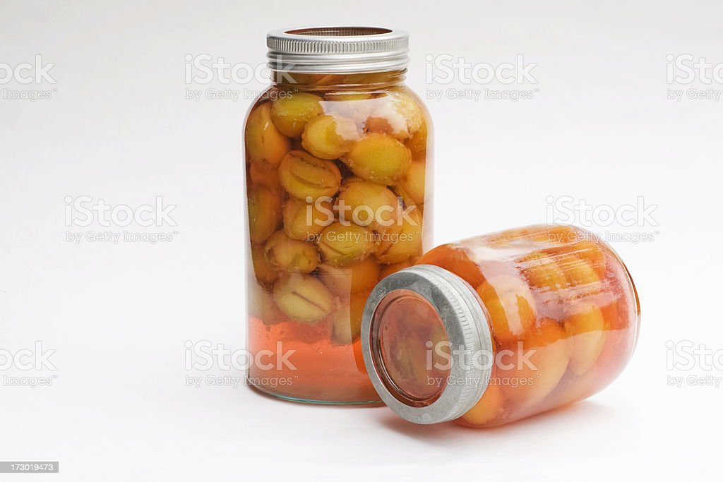 Standing and lying preserved  plums on jars with metal lids. royalty-free stock photo