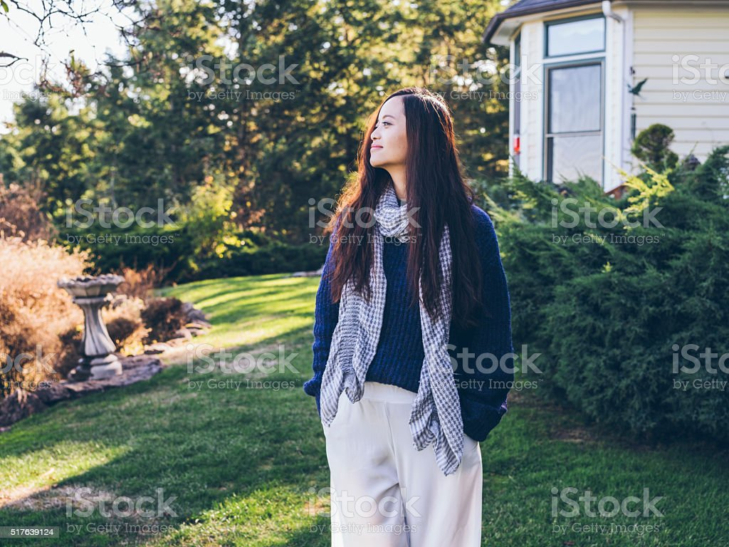 standing asian woman at yard of house stock photo