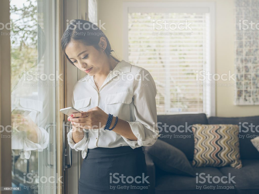 standing asian woman checking phone messages stock photo