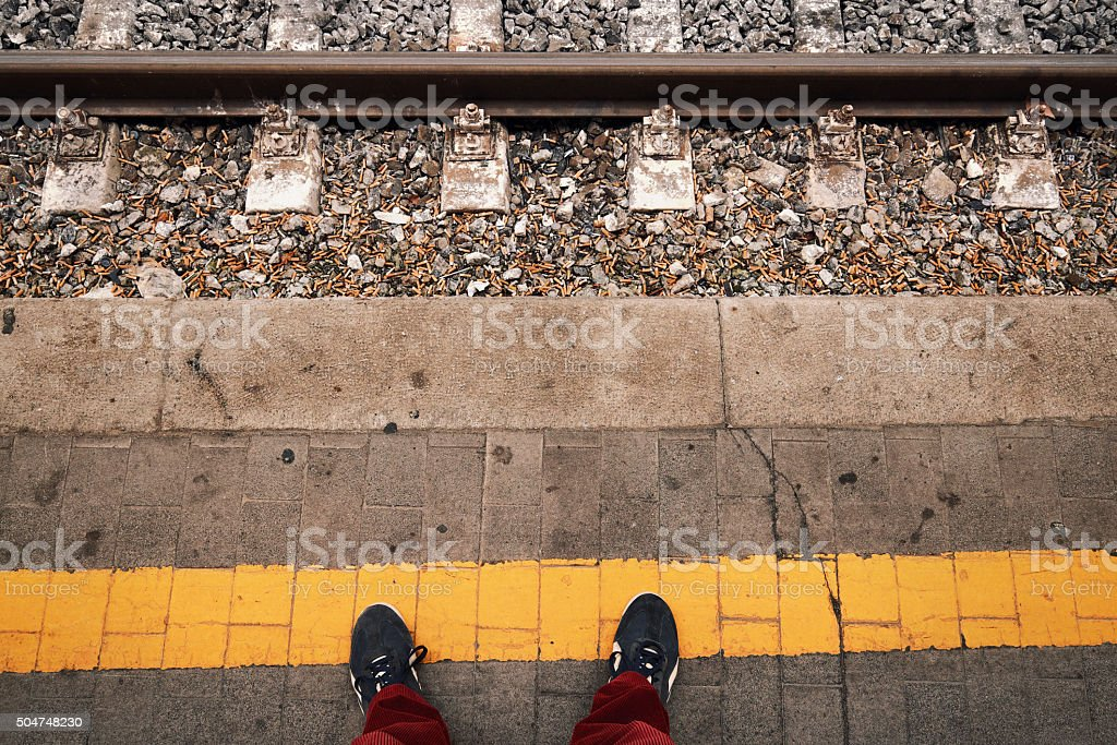 POV standing at the yellow line of railway platform stock photo