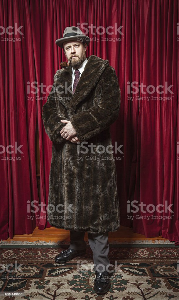 Standing Bearded Man Wearing Fedora, Fur Coat, Pipe in Mouth royalty-free stock photo