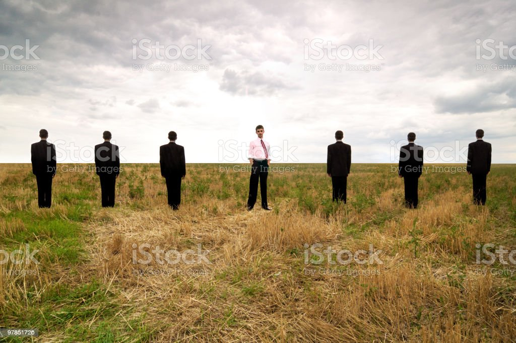 Standing businessman in a line of seven stock photo