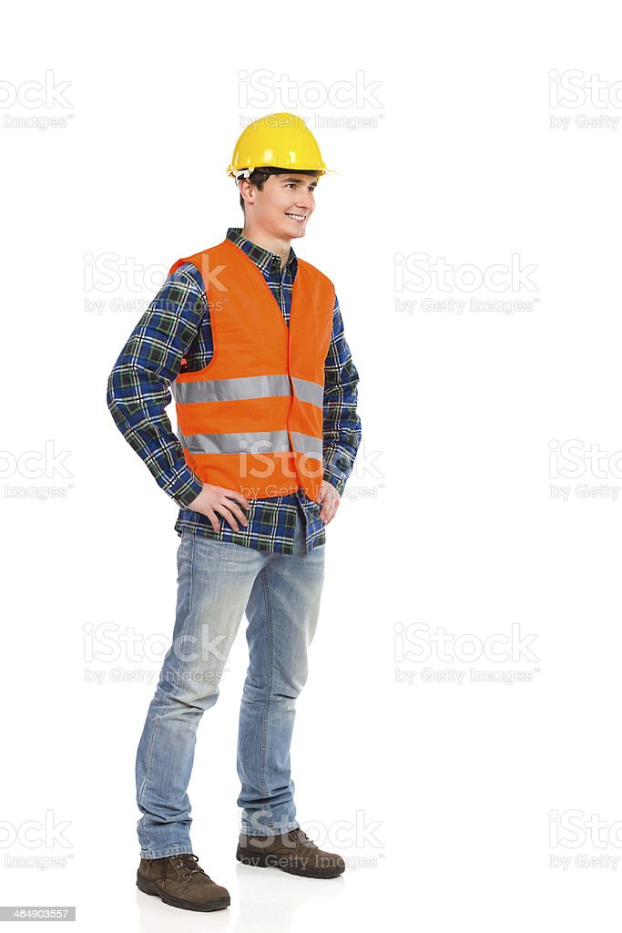 Standing construction worker in yellow helmet and orange waistcoat. stock photo
