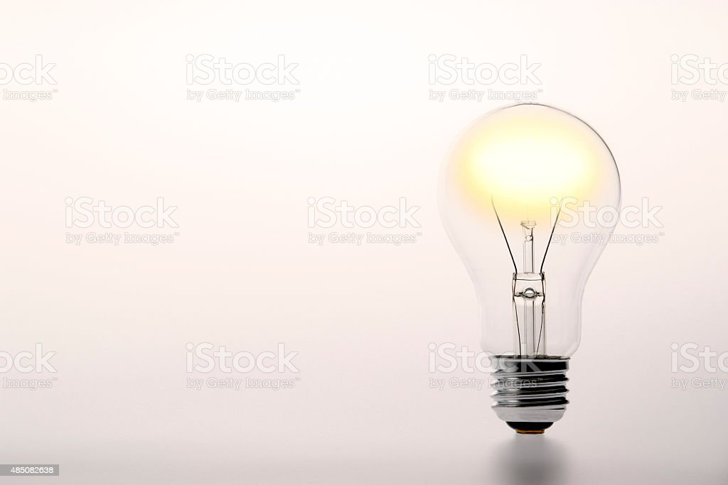 Standing illuminated light bulb with copy space stock photo