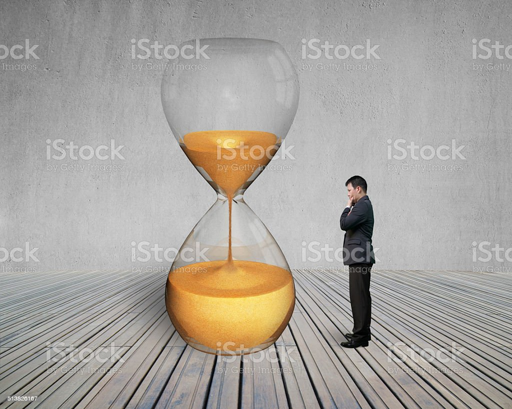 standing manager looking the hourglass stock photo