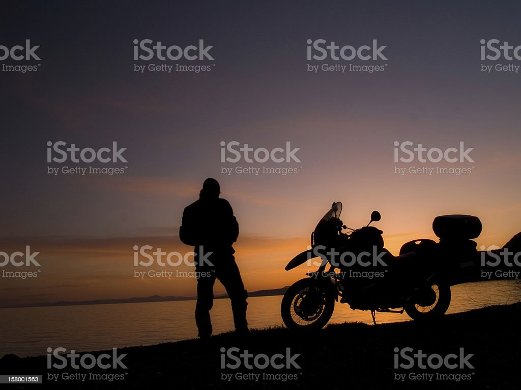 Standing Motorcycle Rider Silhouette at the Sunset stock photo