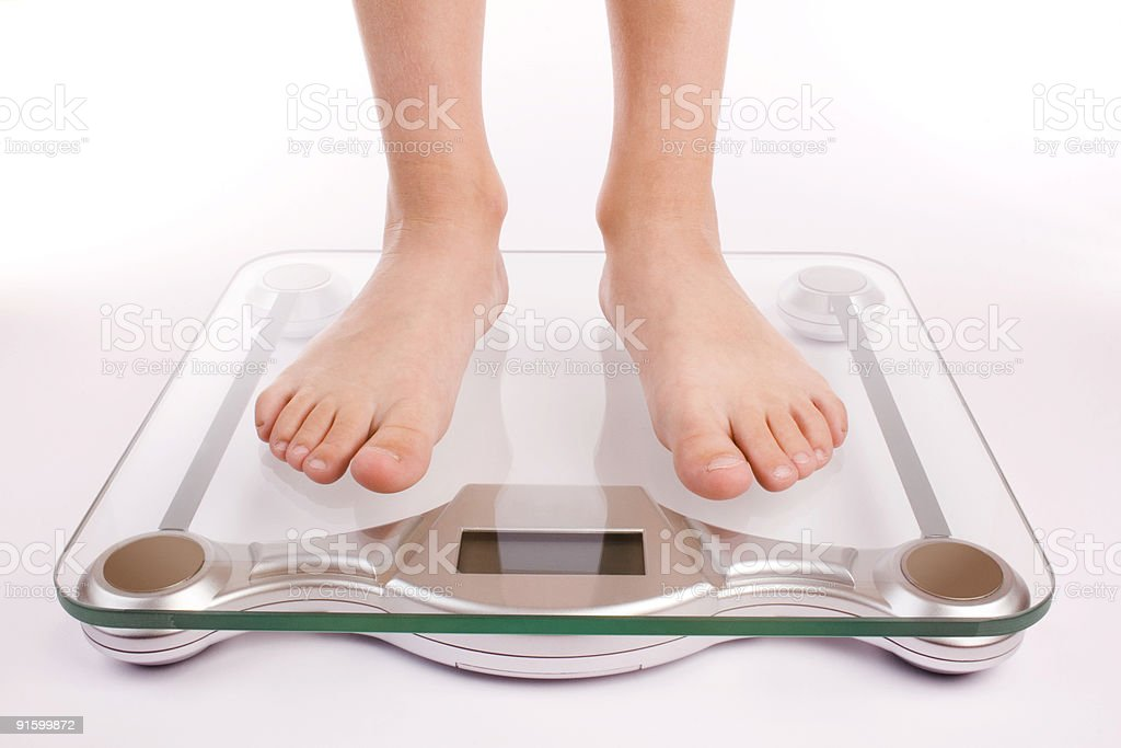 Standing on a modern digital glass scale to check weight stock photo