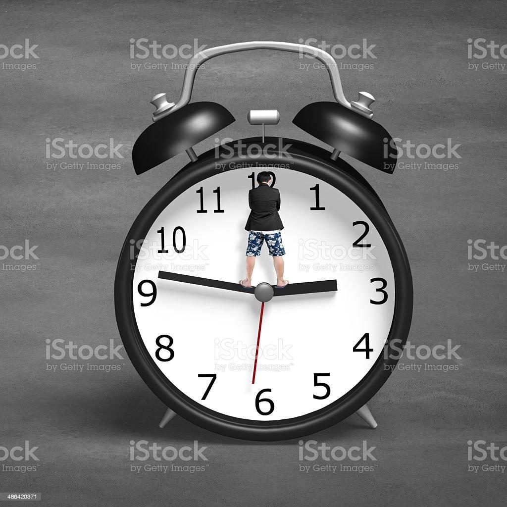 Standing on alarm clock hands stock photo