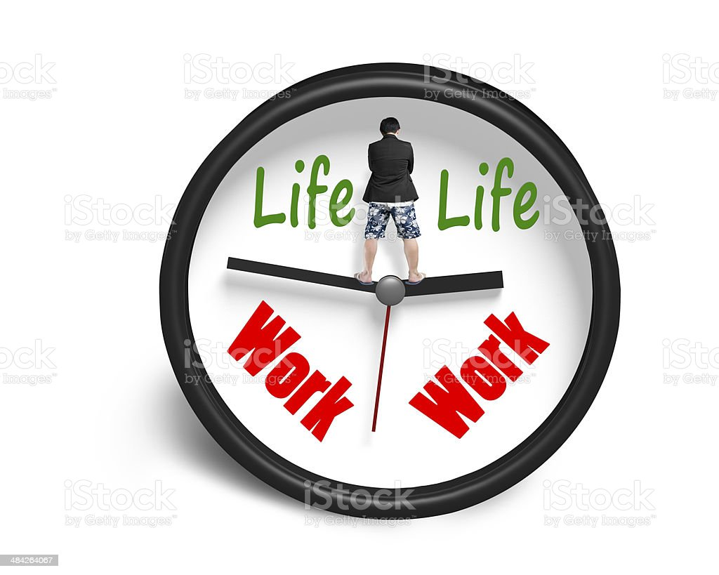 Standing on clock hands with work and life face stock photo